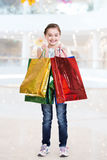 Pretty smiling little girl with shopping bags Stock Photos