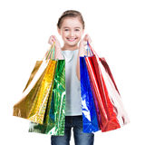 Pretty smiling little girl with shopping bags. Isolated on white Royalty Free Stock Image