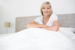 Pretty smiling mature woman sitting on bed Stock Photo