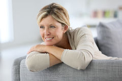 Pretty smiling mature woman sitting on sofa Stock Image