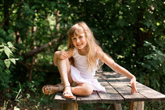 Pretty smiling pensive girl sitting on the old bridge Royalty Free Stock Photography