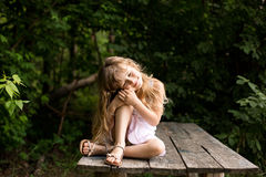 Pretty smiling pensive girl sitting on the old bridge Royalty Free Stock Image