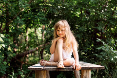 Pretty smiling pensive girl sitting on the old bridge Royalty Free Stock Photo