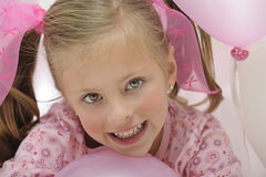 Pretty smiling and playing with pink balloons royalty free stock image
