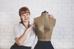 Pretty smiling red-haired woman tailor with mannequin in front o stock photography