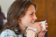 Pretty smiling student drinking a cup of coffee. In college canteen Royalty Free Stock Photo