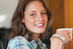 Pretty smiling student having a cup of coffee. In college canteen Royalty Free Stock Images