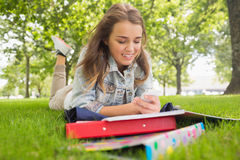 Pretty smiling student lying on the grass sending a text. On college campus Stock Images