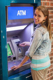 Pretty smiling student withdrawing cash Royalty Free Stock Image
