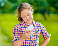 Pretty smiling teenage girl in casual clothes with smartphone. In her hand, looking at screen, reading a message, using Facebook in sunny day in summer park stock photography