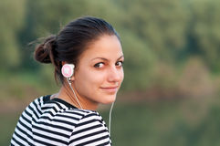 Pretty smiling teenage girl listens to music Stock Image
