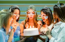 Pretty smiling teenage girls in dresses and crowns holding cake. At birthday party od royalty free stock image