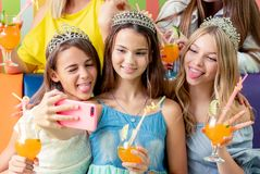 Pretty smiling teenage girls in dresses and crowns sit hugging together holding beverages. And taking selfie at birthday party royalty free stock photography