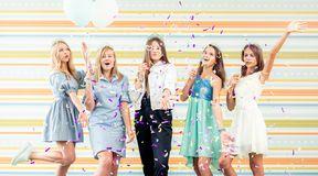 Pretty smiling teenage girls in dresses joyfully raised hands together and run slappers with sparkles at birthday party. Pretty smiling teenage girls in dresses stock photography