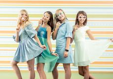 Pretty smiling teenage girls in dresses standing together and holding toy shaped glasses masks at birthday party. Pretty smiling teenage girls in dresses royalty free stock photo