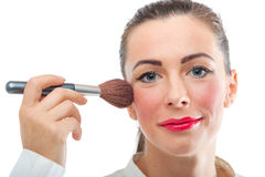 Pretty smiling woman applying make up Stock Photography