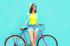 Pretty smiling woman with bicycle over colorful blue background Royalty Free Stock Photography