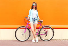 Pretty smiling woman with bicycle over colorful orange Royalty Free Stock Photo