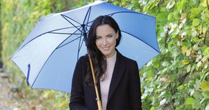 Pretty woman with umbrella. Pretty smiling woman in black jacket holding blue umbrella while walking in autumn park on rainy day stock video