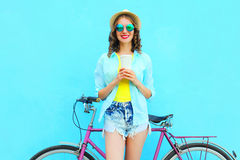 Pretty smiling woman with coffee cup and bicycle over colorful blue Royalty Free Stock Photography