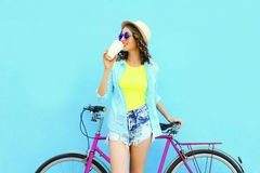 Pretty smiling woman with coffee cup and bicycle over colorful blue background Stock Photo