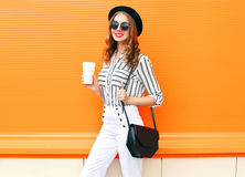Pretty smiling woman with coffee cup wearing fashion black hat white pants handbag clutch over colorful orange Royalty Free Stock Photo