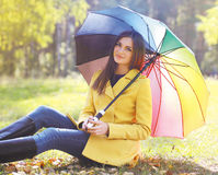 Pretty smiling woman with colorful umbrella outdoors in autumn Stock Image