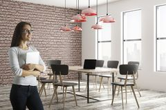 Pretty smiling woman in conference room. Pretty smiling young european woman with laptop standing in modern conference room interior with daylight. 3D Rendering Stock Image