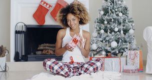 Pretty smiling woman displaying a Christmas gift Stock Photography