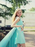 Pretty smiling woman in dress posing in the city Stock Photos