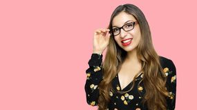 Pretty smiling woman in eyeglasses looking at the camera over pink background royalty free stock photography
