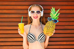 Pretty smiling woman with funny pineapple and fruit juice cup stock photos