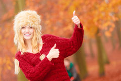 Pretty smiling woman in fur hat with thumb up. Portrait of pretty smiling fashionable woman in fall forest park showing thumb up gesture. Happy gorgeous young Stock Images