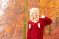 Pretty smiling woman in fur hat with thumb up. Portrait of pretty smiling fashionable woman in fall forest park showing thumb up gesture. Happy gorgeous young Stock Photos