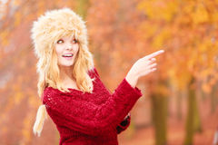 Pretty smiling woman in fur winter hat pointing. Stock Images