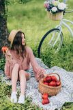 Pretty smiling woman in hat resting on blanket with wicker basket with apples and bicycle parked near. By in park stock photography