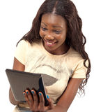 Pretty smiling woman holding digital tablet. African American smiling woman using digital tablet PC against white background Royalty Free Stock Images