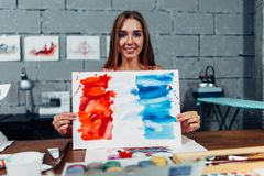 Pretty smiling woman holding a finished watercolor illustration of the flag of France standing in art school classroom.  Royalty Free Stock Photography