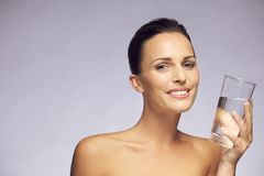 Pretty smiling woman holding a glass of clean water Royalty Free Stock Image
