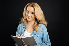 Pretty smiling woman making some notes. Be attentive. Attractive female with blonde curly hair wearing jeans shirt holding notebook in left hand while writing Royalty Free Stock Images