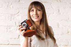 Pretty smiling woman with old film camera on white brick wall Stock Photography
