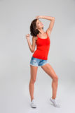 Pretty smiling woman posing on white background. Pretty smiling curly young woman in red top, jeans shorts and white sneackers posing on white background royalty free stock photo