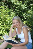 Pretty smiling woman reading in the garden. Pretty smiling young blond woman wearing summer shorts reading in the garden in the shade of a leafy green tree Royalty Free Stock Image