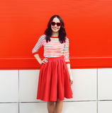 Pretty smiling woman in red sunglasses and dress Stock Images