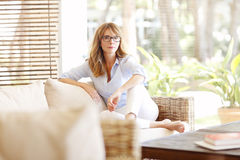 Pretty smiling woman relaxing on couch Stock Photo
