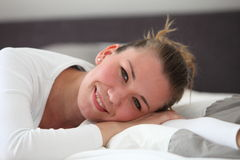 Pretty smiling woman resting on her bed. Lying on her stomach with her head on her hands with a smile of contentment royalty free stock image