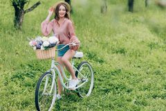 Pretty smiling woman on retro bicycle with wicker basket full of flowers. In forest royalty free stock photos