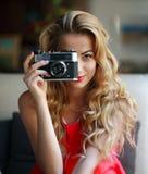 Pretty smiling woman with retro film camera Stock Image