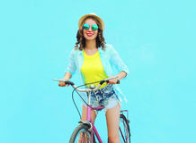 Pretty smiling woman rides a bicycle over colorful blue Stock Photos