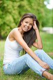 Pretty Smiling Woman Sitting on Grassy Ground Royalty Free Stock Photos